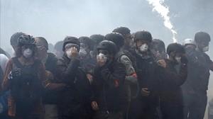Manifestantes se protegen de los gases lacrimógenos.
