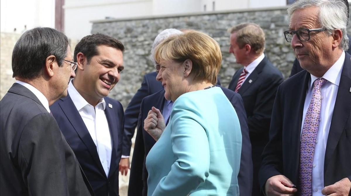 Merkel (centro), con Tsipras (izq) y Juncker (derecha), este viernes en Bratislava.