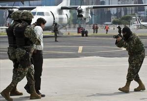 El narcotraficante mexicano Joaquín Guzmán Loera alias El Chapo Guzmán , es escoltado por infantes de marina en la Ciudad de México.