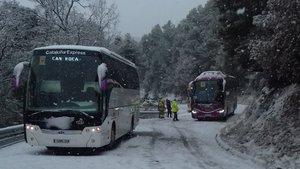 Los autocars bloqueados por la nieve, antes de la intervención de la máquina quitanieves, en su acceso a El Port del Comte.