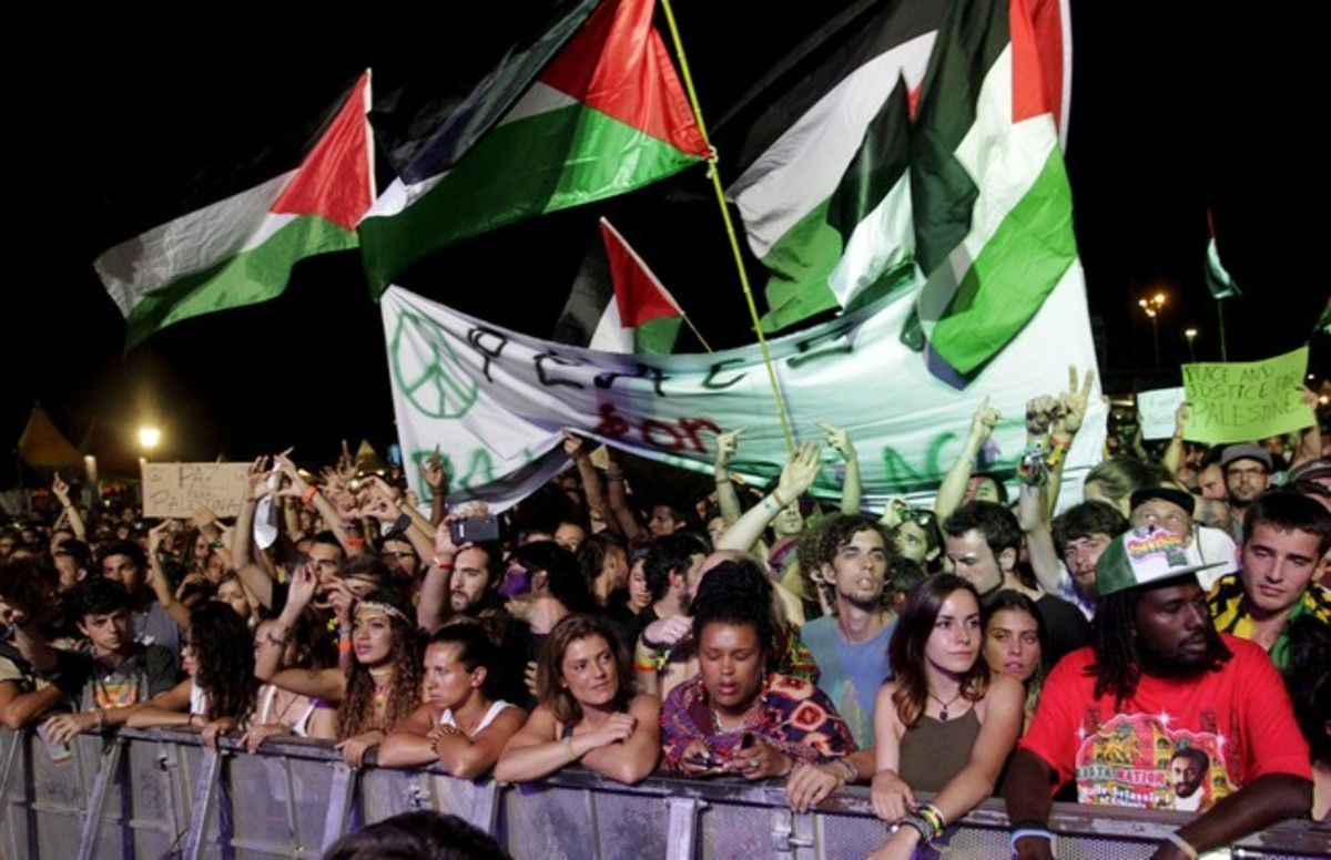 Palestinian flags fly as U.S. Jewish musician Matisyahu performs on stage during the Rototom Sunsplash festival in Benicassim, August 23, 2015. The Spanish reggae festival, bowing to an international outcry, on Wednesday reversed its decision to cancel an invitation to Matisyahu because he had failed to spell out his views on Palestinian statehood. The festival had asked the musician, who fuses reggae, hip-hop and rock with Jewish influences, to make a public statement about his views on Palestinians' right to their own state and withdrew the invitation when he did not respond. The letters on the banner and placards read Peace for Palestine. REUTERS/Heino Kalis