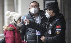 Personal de seguridad comprueba la temperatura coproral de los pasajeros en el muelle del río Yangtze, en la ciudad china de Wuhan.