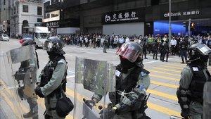 Policía antidisturbios vigila a manifestantes en el distrito financiero de Hong Kong.
