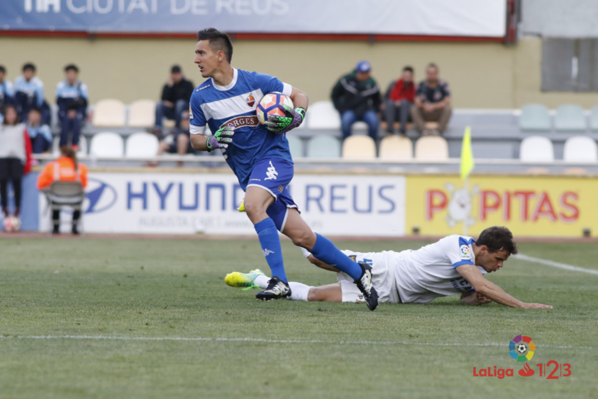 El portero del Reus, Edgar Badia, ataja el balón ante un delantero del UCAM Murcia.