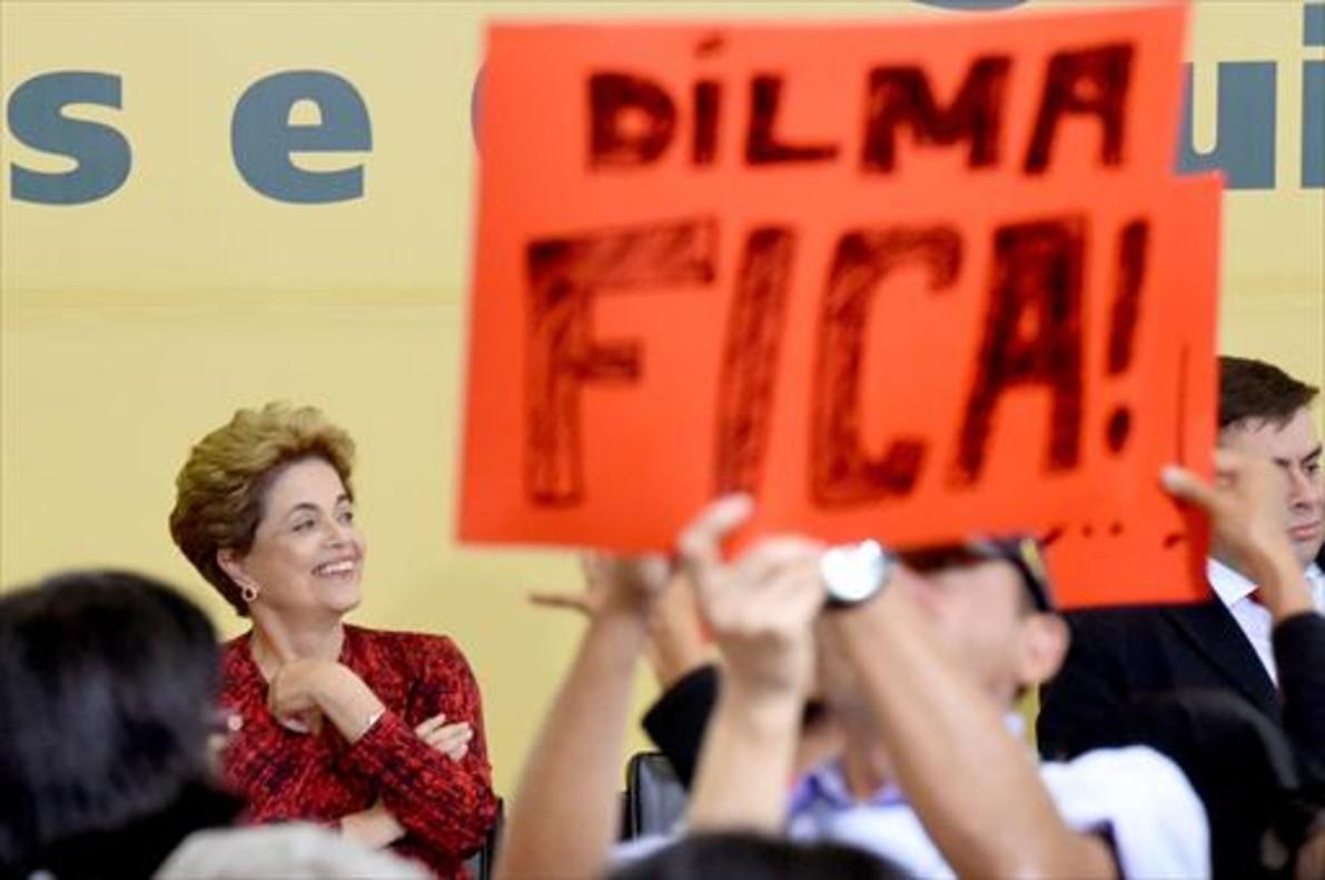 Rousseff sonríe ayer en un acto en Brasilia, mientras un asistente sostiene un cartel que dice «Dilma se queda».
