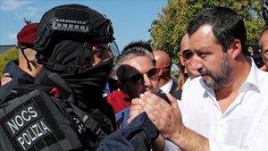 Salvini da la mano a un miembro de la policia especial italiana en un acto commemorativo