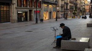 Una persona mayor sola en el Portal de l'Àngel de Barcelona.