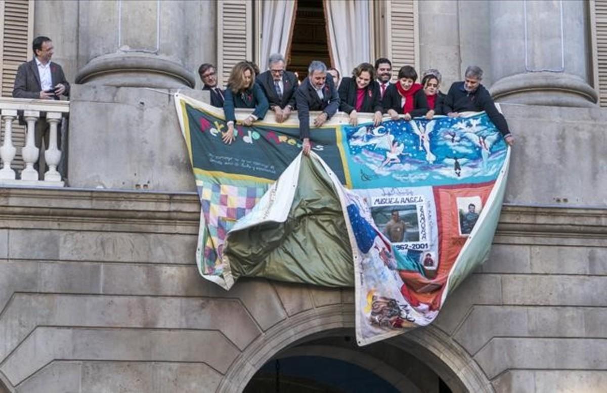Colocación del tapiz en la fachada del Ayuntamiento de Barcelona, donde se recuerda a los fallecidos por el sida en el último año.