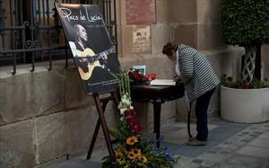 Una dona firma al llibre de condol davant una fotografia de Paco de Lucía a Algesires.