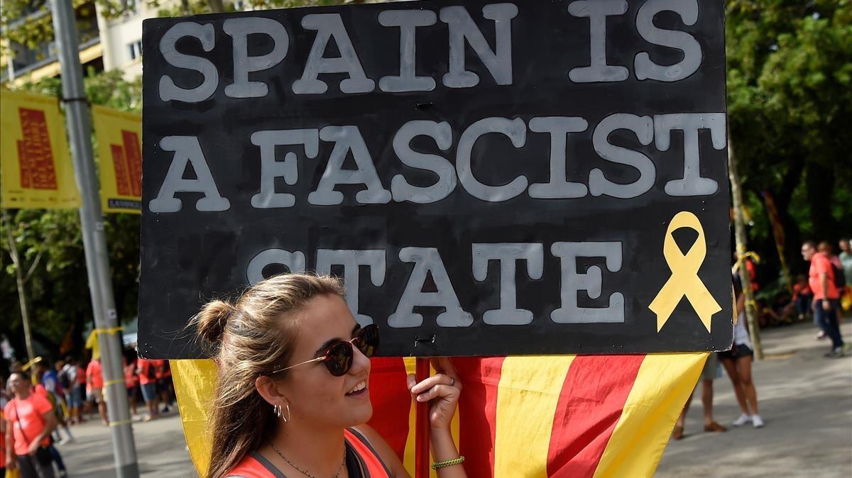 Una joven con un pancarta en la que se lee:España es un estado fascista