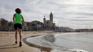 Una mujer hace ejercicio en la playa de Sitges, el pasado día 4.