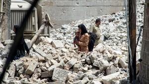 Una mujer iraquíe con un niño camina entre las ruinas de Mosul, un año después de la liberación de la ciudad