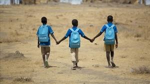Unos niños africanos se dirigen al colegio.