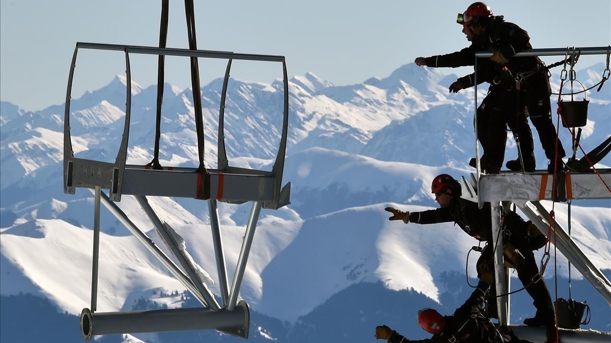 Varios técnicos intentan alcanzar una pieza de la estructura metálica durante la instalación de la plataforma en la cima del Pico de Midi, una de las montañas más altas de Francia, en Bagneres-de-Bigorre, el 30 de enero.