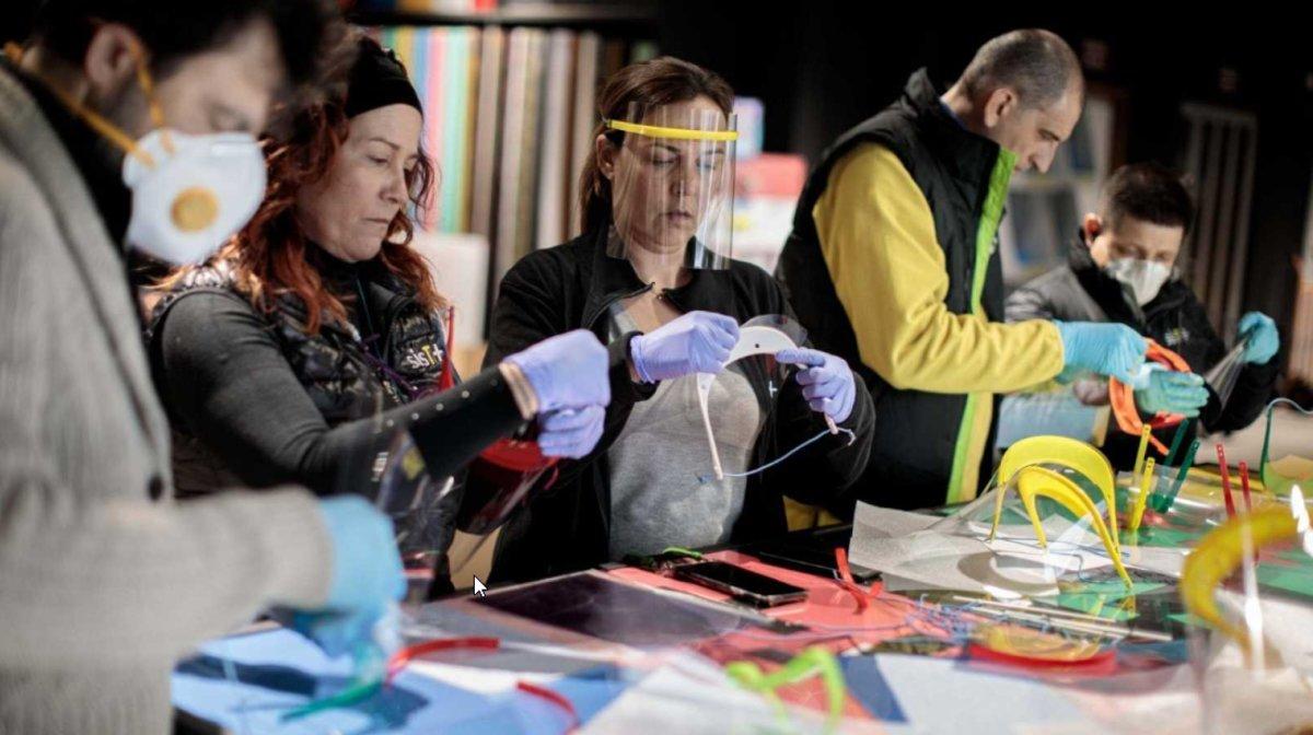 Voluntarios del movimiento Coronavirus Makers ensamblan piezas de viseras.