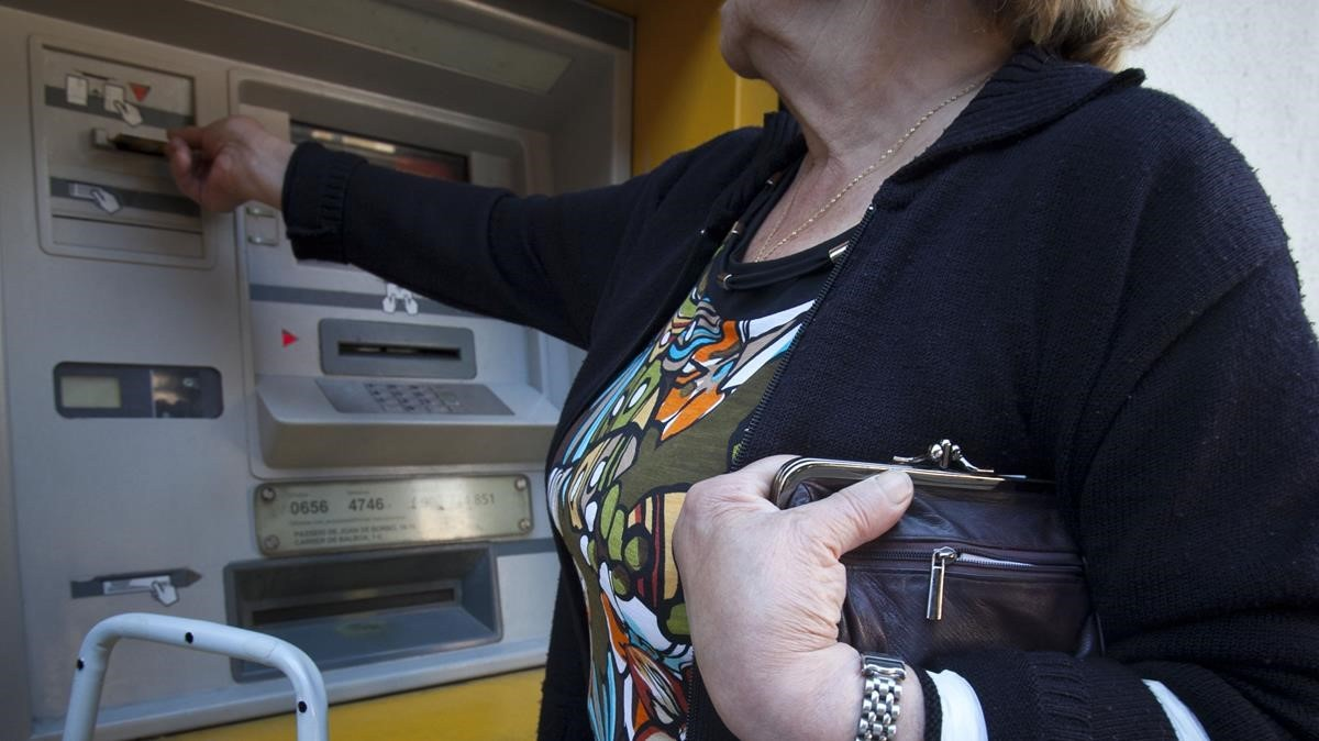Una mujer mayor saca dinero de una cajero automático.