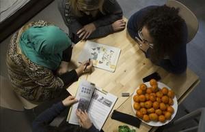 Dos técnicas de Creu Roja imparten una clase de catalán en la Casa Bloc de Barcelona a dos refugiadas.