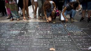 Los transeúntes escriben sus condolencias con tizas sobre el pavimento de la Rambla el 19 de agosto de 2017.
