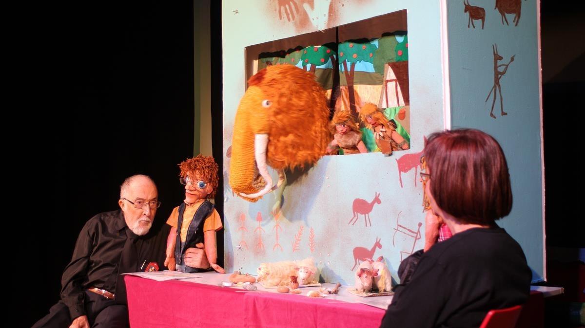 Integrantes de una asociación de personas mayores del Raval interpretan un espectáculo de marionetas sobre la prehistoria.