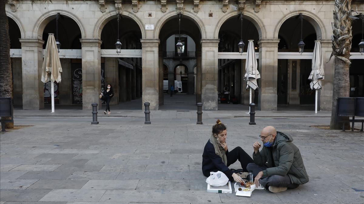 Dos personas toman algo en el suelo de la plaza Reial de Barcelona al estar cerrados los bares en Catalunya.