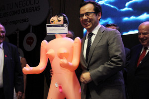 Chiles economy minister Luis Cespedes holds up an inflatable doll during an event of the exporters association Asexma in Santiago