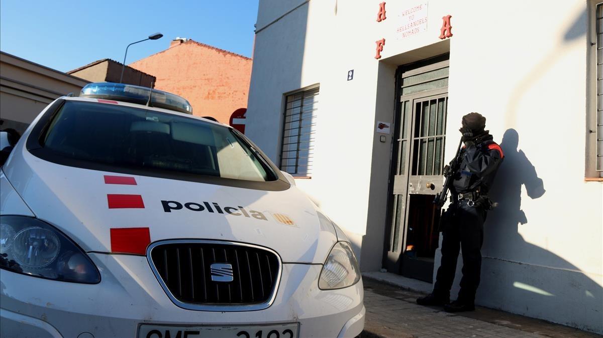 Un agente de los Mossos custodia la entrada a la sede de Los Ángeles del Infierno en Sabadell.