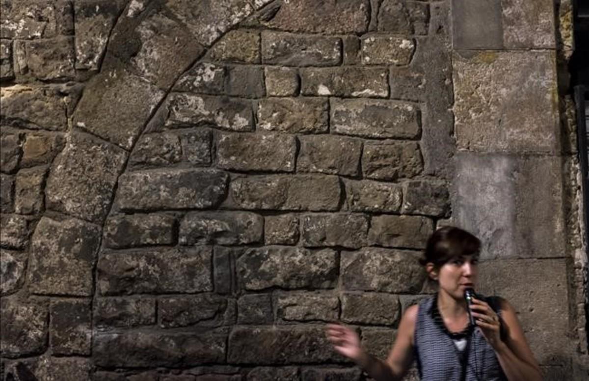 """Calle de la Flor de Lliri. Esta pared es la versión barcelonesa de las caras de Bélmez. Si se mira fijamente, se encuentran varias caras. Serían la proyección de la gente a la que han matado aquí"""", dice la guía, Cristina Belenguer."""