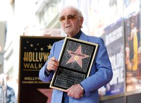 El cantante franco-armenio Charles Aznavour posa con su estrella en el paseo de la Fama de Hollywood.