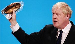 Boris Johnson sostiene un pescado ahumado durante una intervención en Londres.