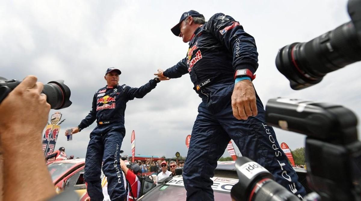 Carlos Sainz, a la derecha, felicita, sobre su Peugeot, a su copiloto Lucas Cruz.