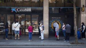 Cola de clientes antes una sucursal de Caixabank en Barcelona, el 26 de mayo.