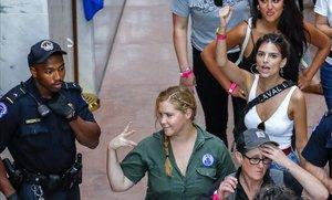 La comediante estadounidense Amy Schumer (centro) y la modelo estadounidense Emily Ratajkowski (derecha, detrás), en el momento de ser detenidas junto a otros manifestantes contra la elección de Kavanaugh.