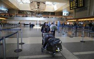 Una turista protegiéndose del coronavirus en un aeropuerto.
