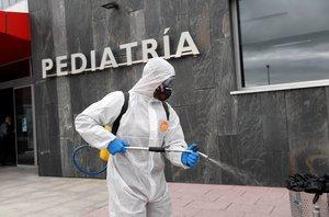 Un miembro de la Unión Militar de Emergencias desinfecta un acceso al Hospital Universitario Central de Asturias para combatir el coronavirus.