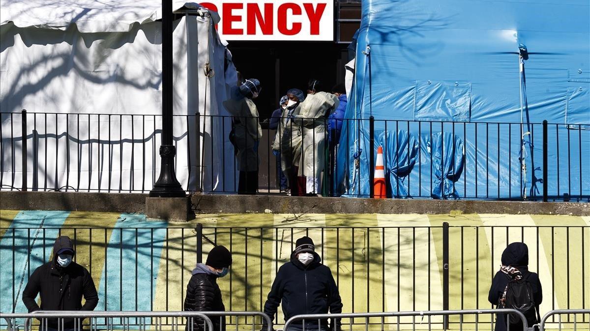 Un grupo de personas hace cola para hacerse la prueba del coronavirus en el hospital Elmhurst de Queens, en Nueva York.