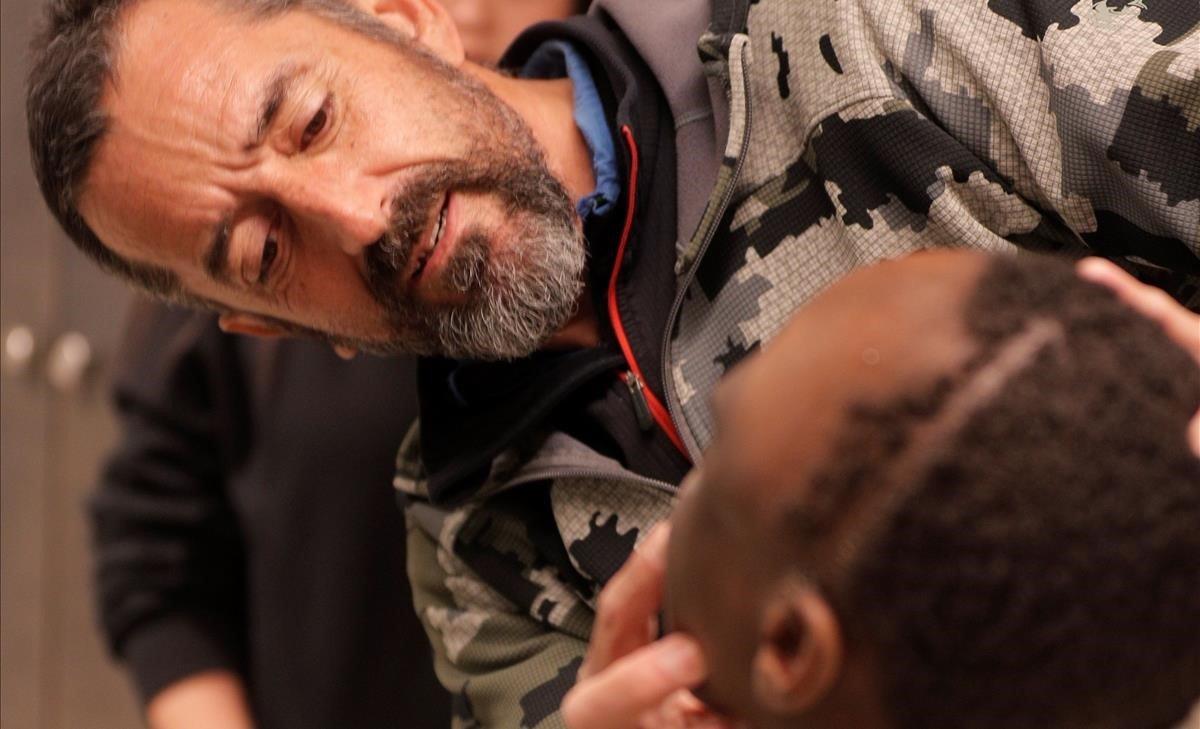 El cirujano Pedro Cavadas observa la cara de Emmanuel, el niño al que ha extirpado un tumor