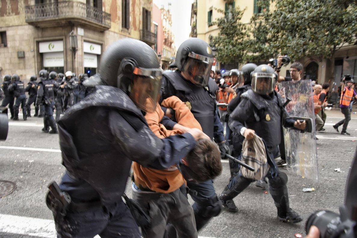 Dos policías con uno de los manifestantes detenidos en Via Laietana.