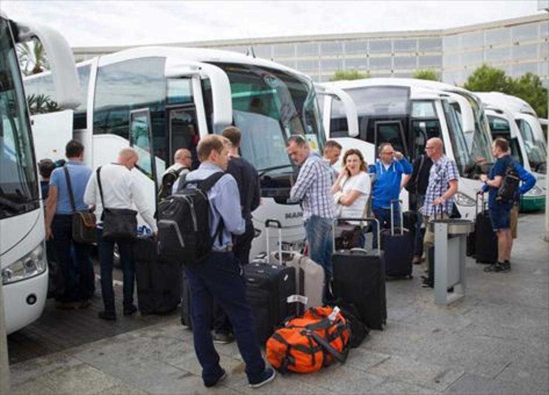 Un grupo de turistas esperan en el aeropuerto de Palma a que los autobuses los lleven a sus hoteles.