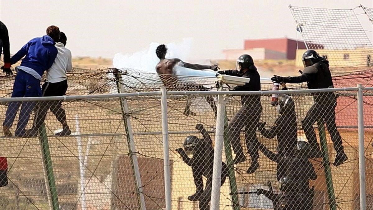 Guardias civiles rocían con un extintor a inmigrantes que intentaban usar mecheros en la valla de Melilla.