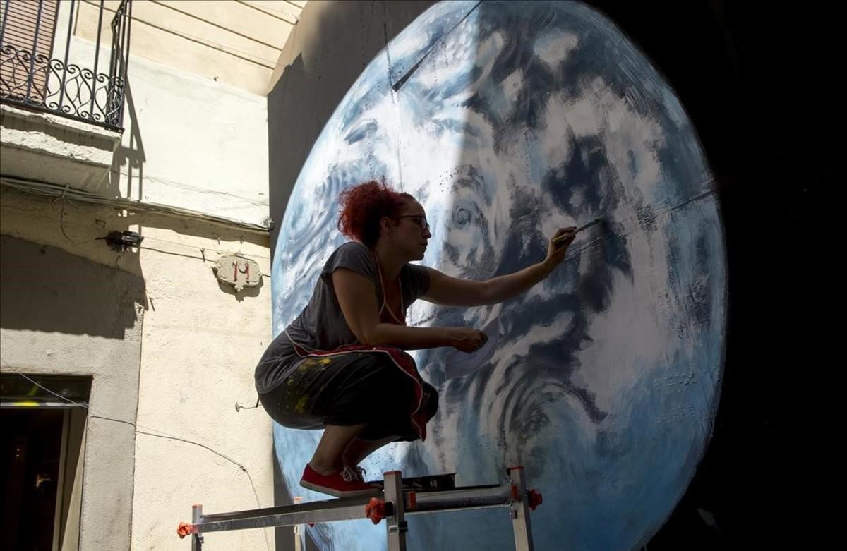 Una mujer trabaja en la decoración de la calle Llibertat, que evoca películas espaciales.
