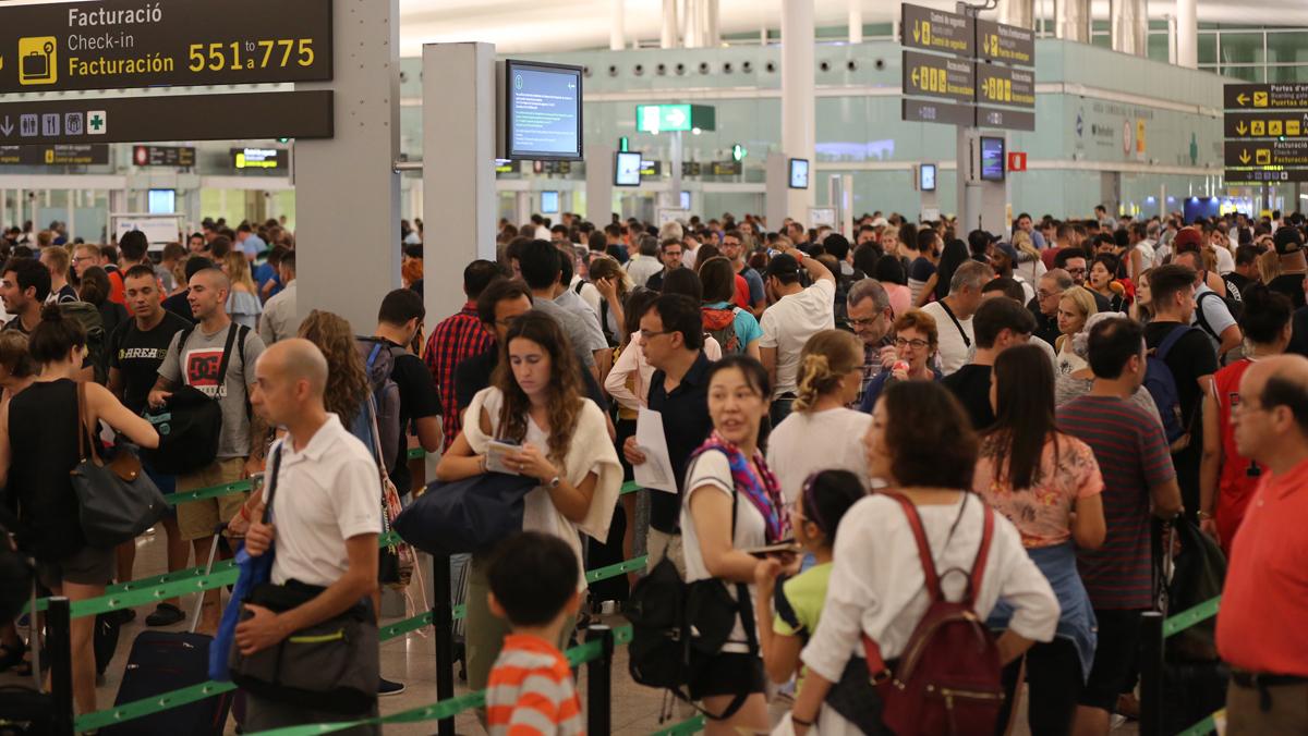 Colas para pasar el control de seguridad en la T1 del aeropuerto de El Prat, este jueves.