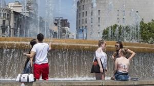 Unas personas se remojan en una fuente de plaza Catalunya este verano en plena ola de calor.