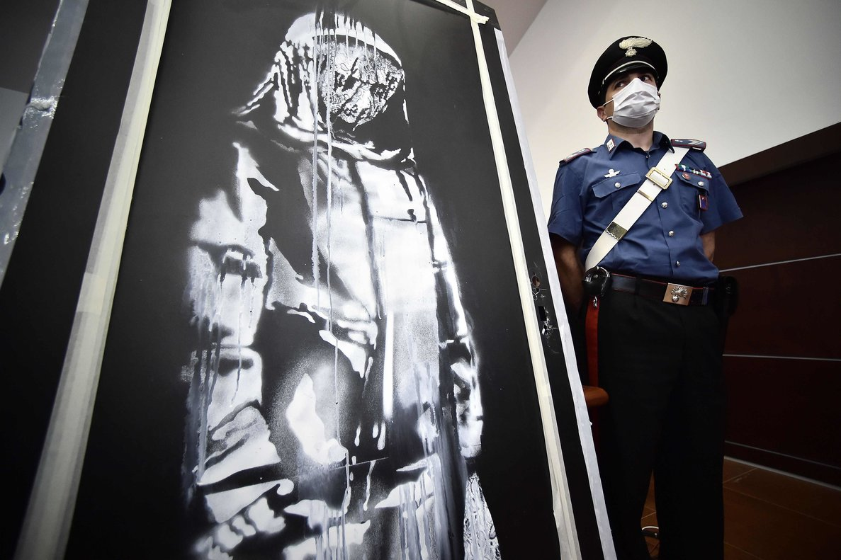 Un policía junto al cuadro de Banksy recuperado en Italia.