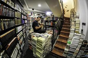 Ricard Ruiz Garzón en su biblioteca, sentado sobre libros de los que tiene que desprenderse, en Santa Coloma de Gramenet.