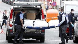 Empleados de una funerariaportan el cuerpo de una persona fallecida.