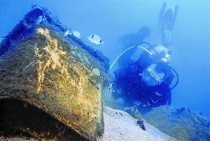 Un submarinista retira un contenidor descombraries enfonsat a prop de lespigó de la Mar Bella, a Barcelona, el novembre del 2011.
