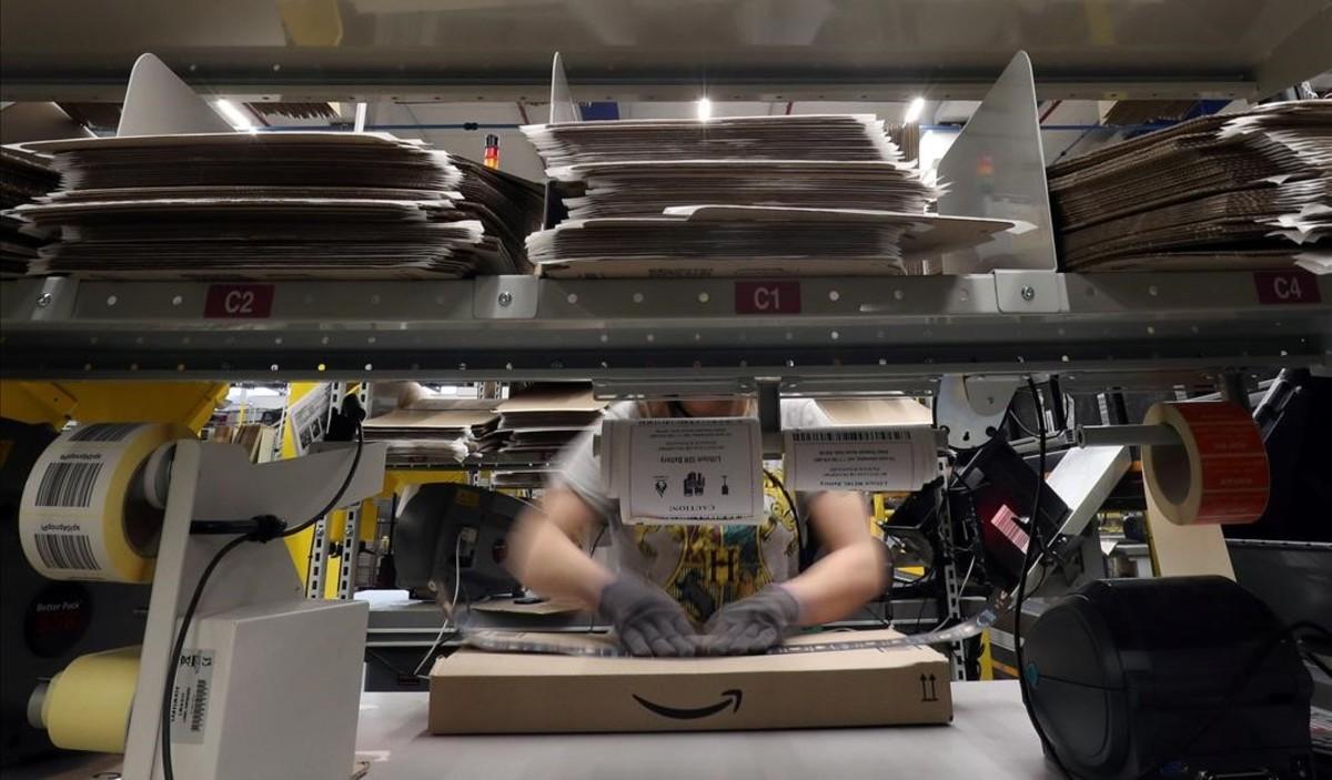 Un trabajador prepara un pedido en una caja de Amazon.