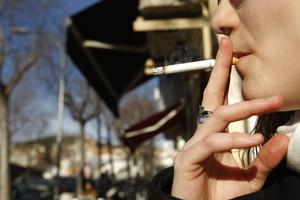 Una dona fuma al carrer, després de l'aplicació de la llei contra el tabac, en una imatge del 2011.