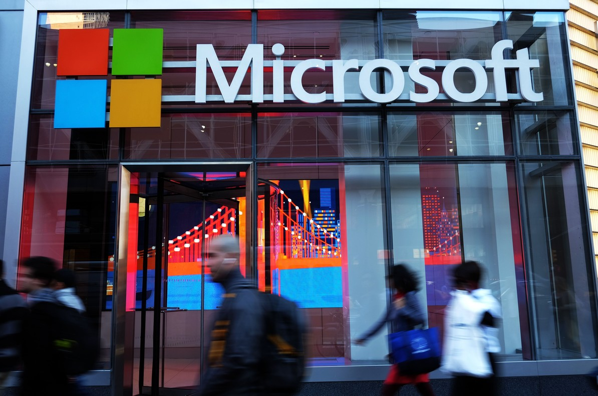 (FILES) This file photo taken on October 06, 2015 shows people walk past a Microsoft office in New York.