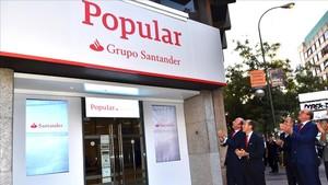 Directivos del Santander ante una de las primeras oficinas del Popular que ya ha adoptado la imagen corporativa del grupo cántabro, en Madrid.